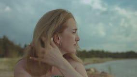 Ritratto della donna pensierosa dello zenzero che riposa alla spiaggia archivi video