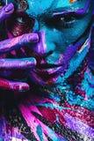 Ritratto della donna in pittura blu e rosa con le dita sul fronte Fotografia Stock