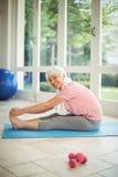 Ritratto della donna senior che esegue allungando esercizio a casa Immagini Stock
