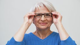 Ritratto della donna senior che mette i suoi vetri sopra archivi video