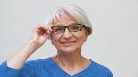 Ritratto della donna senior che regola i suoi vetri stock footage