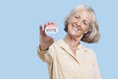 Ritratto della donna senior che tiene un distintivo di elezione contro il fondo blu Fotografia Stock