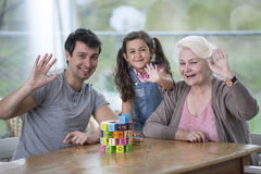 Ritratto della donna senior con le mani d'ondeggiamento della nipote e del figlio alla tavola Fotografie Stock Libere da Diritti