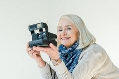 Ritratto della donna senior sorridente che tiene la retro macchina fotografica della foto Immagini Stock Libere da Diritti