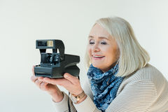 Ritratto della donna senior sorridente che tiene la retro macchina fotografica della foto Immagine Stock Libera da Diritti
