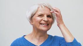 Ritratto della donna senior sorridente che tocca i suoi capelli video d archivio