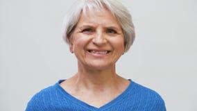 Ritratto della donna senior sorridente sopra grigio archivi video