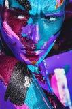 Ritratto della donna seria nei colpi variopinti della pittura Immagini Stock