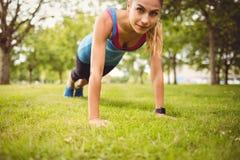 Ritratto della donna sicura che si esercita sull'erba Fotografia Stock
