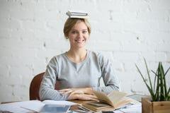 Ritratto della donna sorridente allo scrittorio, libri su lei capa Fotografie Stock Libere da Diritti