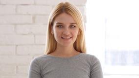 Ritratto della donna sorridente che esamina macchina fotografica in ufficio Fotografie Stock Libere da Diritti