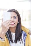 Ritratto della donna sorridente che guarda messaggio nel telefono immagini stock libere da diritti