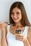 Ritratto della donna sorridente che mangia yogurt con l'avena e le bacche Immagini Stock