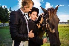 Ritratto della donna sorridente che sta con l'uomo dal cavallo sul campo Immagine Stock Libera da Diritti