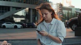 Ritratto della donna sorridente che usando riconoscimento della voce dello smartphone Giovane ragazza caucasica che cammina con l video d archivio