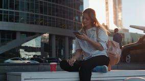Ritratto della donna sorridente che usando riconoscimento della voce dello smartphone Giovane ragazza caucasica che cammina con l archivi video