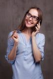 Ritratto della donna sorridente con i vetri che parlano dal cellulare vicino alla parete grigia del fondo Fotografia Stock