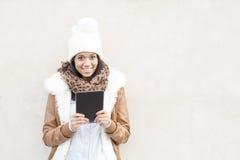 Ritratto della donna sorridente con il computer della compressa e del cofano su wal Fotografia Stock Libera da Diritti
