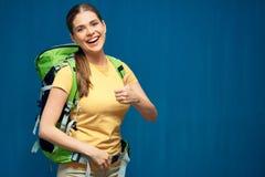 Ritratto della donna sorridente con lo zaino turistico che dà pollice su Immagine Stock Libera da Diritti