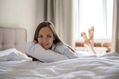 Ritratto della donna sorridente a letto che si trova sul suo stomaco fotografia stock libera da diritti