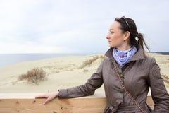 Ritratto della donna, stando sulla lingua della sabbia, guardante lontano, copyspace Immagine Stock