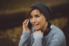 Ritratto della donna triste che si siede da solo nella foresta con lo smartphone Concetto di solitudine Millenial che si occupa d Immagini Stock