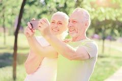 Ritratto della famiglia allegra che fa i selfies Immagine Stock