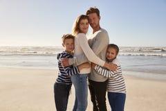Ritratto della famiglia amorosa che abbraccia sulla spiaggia di inverno immagine stock libera da diritti