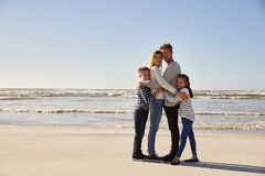 Ritratto della famiglia amorosa che abbraccia sulla spiaggia di inverno fotografia stock