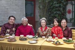 Ritratto della famiglia che gode del pasto cinese in cinese l'abbigliamento del cinese tradizionale Immagine Stock