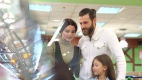 Ritratto della famiglia che sceglie pane ed i dolci nella sezione del forno in supermercato archivi video