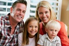 Ritratto della famiglia che si siede sul sofà a casa Fotografia Stock