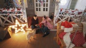 Ritratto della famiglia con pochi derivato e cane sul portico con l'albero di Natale video d archivio