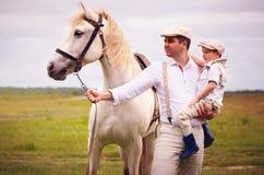 Ritratto della famiglia dell'agricoltore che sta sul campo con il cavallo Fotografie Stock