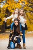 Ritratto della famiglia delle sorelle nel parco giallo di autunno Fotografia Stock