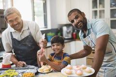 Ritratto della famiglia di diverse generazioni felice che prepara insieme alimento dolce nella cucina fotografia stock libera da diritti