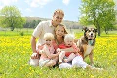 Ritratto della famiglia e del cane felici nel prato del fiore Immagini Stock Libere da Diritti