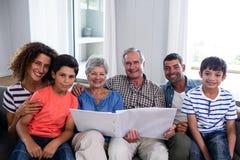 Ritratto della famiglia felice che si siede sul sofà e che esamina album di foto immagini stock libere da diritti