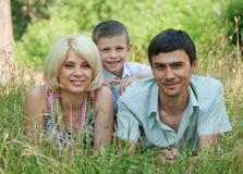 Ritratto della famiglia felice che si trova giù sull'erba. Fotografia Stock