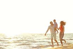 Ritratto della famiglia felice e del bambino che godono del tramonto nello svago di estate immagine stock