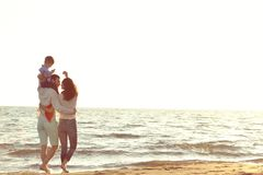 Ritratto della famiglia felice e del bambino che godono del tramonto nello svago di estate fotografia stock