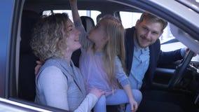 Ritratto della famiglia felice nel concessionario auto, giovani genitori con la ragazza del bambino che sorride e che abbraccia m
