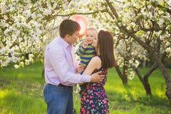Ritratto della famiglia felice padre, madre, abbracciare del bambino e bacio immagini stock libere da diritti