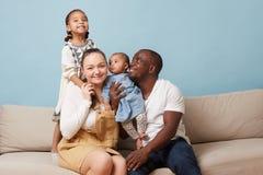 Ritratto della famiglia multietnica felice che si siede sullo strato e che si diverte a casa fotografia stock