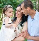Ritratto della famiglia nel parco della città di estate, genitori con il bambino, stagione estiva, erba verde ed alberi Fotografia Stock Libera da Diritti