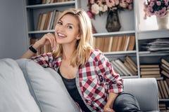 Ritratto della femmina bionda sorridente in una stanza con i libri di lettura o Fotografia Stock Libera da Diritti