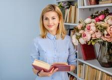 Ritratto della femmina positiva bionda con il libro Immagini Stock Libere da Diritti
