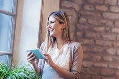 Ritratto della femmina sorridente dei giovani che per mezzo del dispositivo digitale della compressa Immagine Stock Libera da Diritti