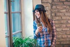 Ritratto della femmina sorridente dei giovani che per mezzo dello Smart Phone Immagini Stock Libere da Diritti