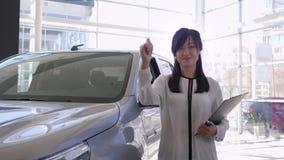 Ritratto della femmina sorridente del responsabile che dà i pollici positivi di gesto su vicino alla nuova automobile nel centro